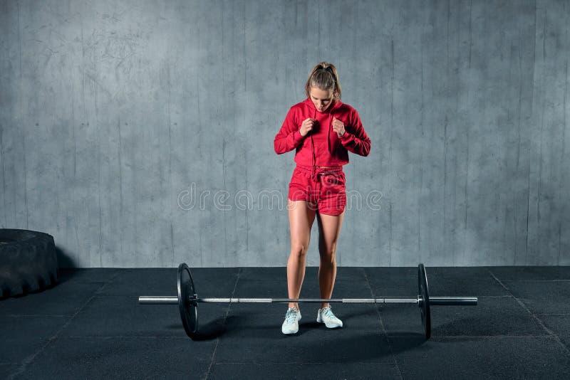Lyftande skivstång för härlig konditionkvinna Lyftande vikter för sportig kvinna Färdig flicka som övar byggnadsmuskler arkivbild