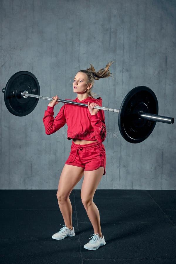 Lyftande skivstång för härlig konditionkvinna Lyftande vikter för sportig kvinna Färdig flicka som övar byggnadsmuskler fotografering för bildbyråer