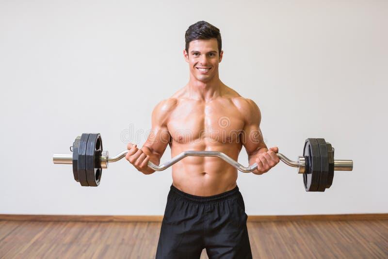 Lyftande skivstång för Shirtless muskulös man i idrottshall royaltyfri foto