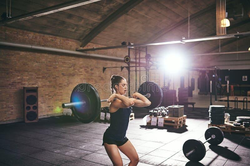 Lyftande skivstånger för ung muskulös kvinnlig i idrottshall arkivbild