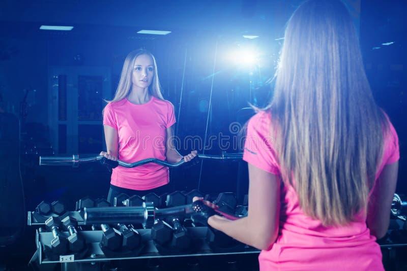 Lyftande vikt för attraktiv sportig flicka i idrottshall Kvinnlig idrottsman nen som gör fysisk övning Blond konditionflicka i sp royaltyfri bild