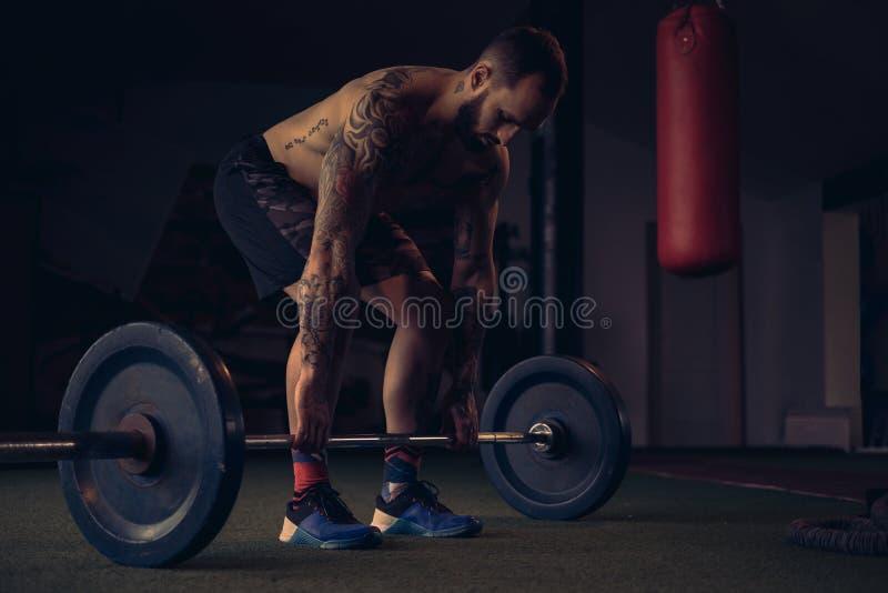 Lyftande vikt för manlig idrottsman nenstart från golvet arkivfoton