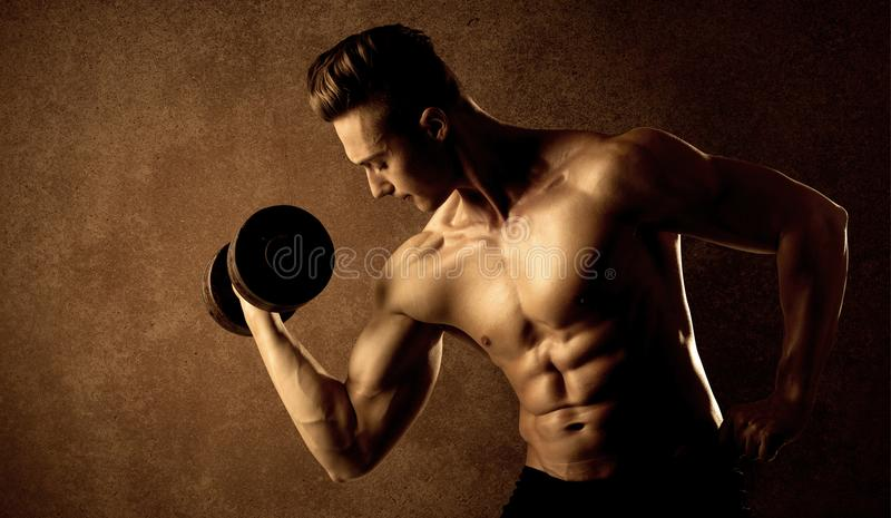 Lyftande vikt för muskulös passformkroppsbyggareidrottsman nen royaltyfri bild