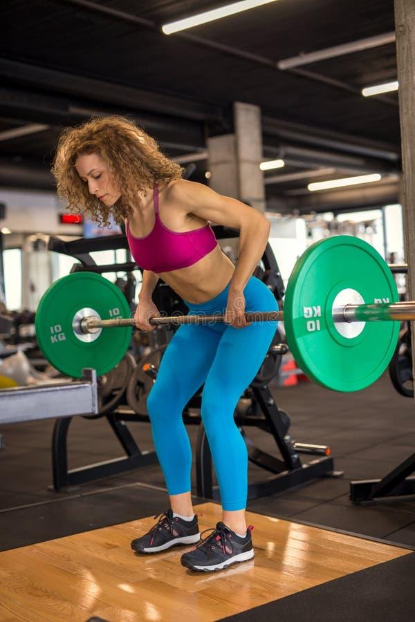 Lyftande vikter för härlig idrotts- kvinna på idrottshallen royaltyfri bild