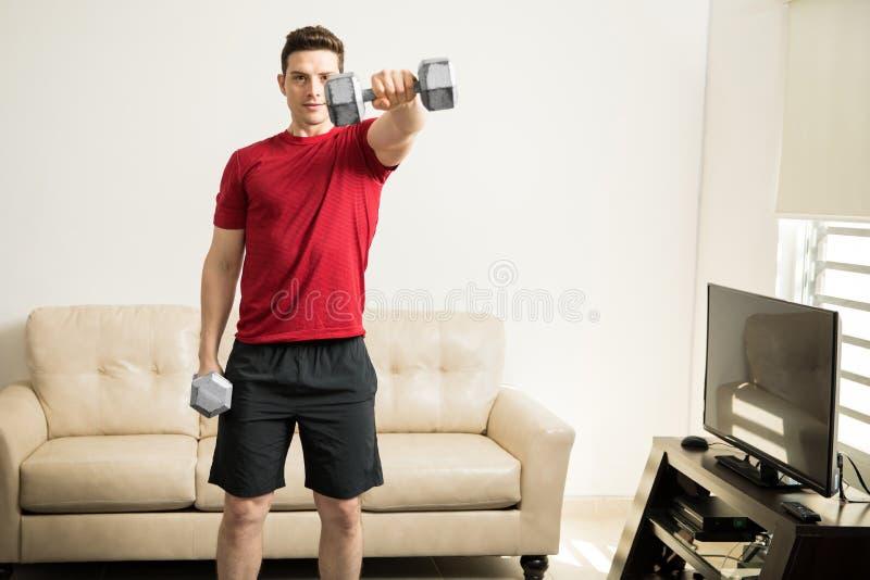 Lyftande vikter för idrotts- man i vardagsrummet arkivfoto