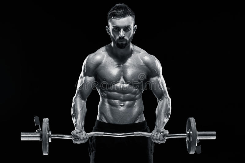 Lyftande vikter för muskulös man över mörk bakgrund royaltyfri bild
