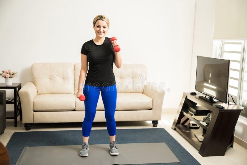 Lyftande vikter för nätt flicka hemma fotografering för bildbyråer