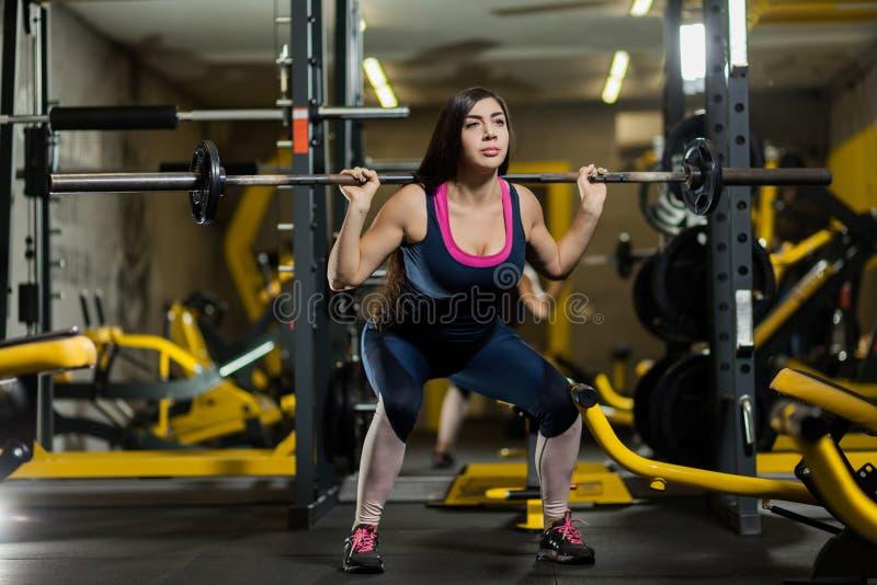 Lyftande vikter för sportig kvinna Färdig flicka som övar byggnadsmuskler Kondition och bodybuilding arkivfoto