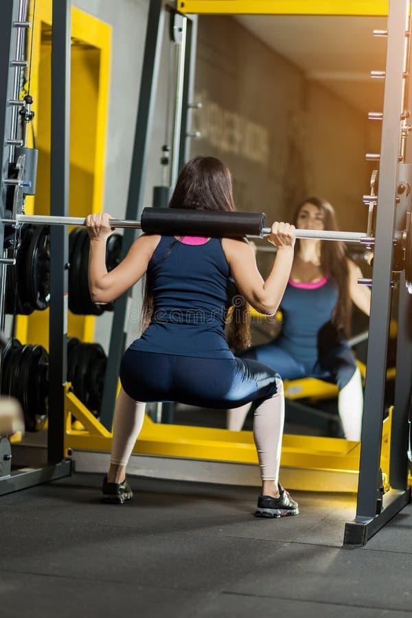 Lyftande vikter för sportig kvinna Färdig flicka som övar byggnadsmuskler Kondition och bodybuilding royaltyfri fotografi