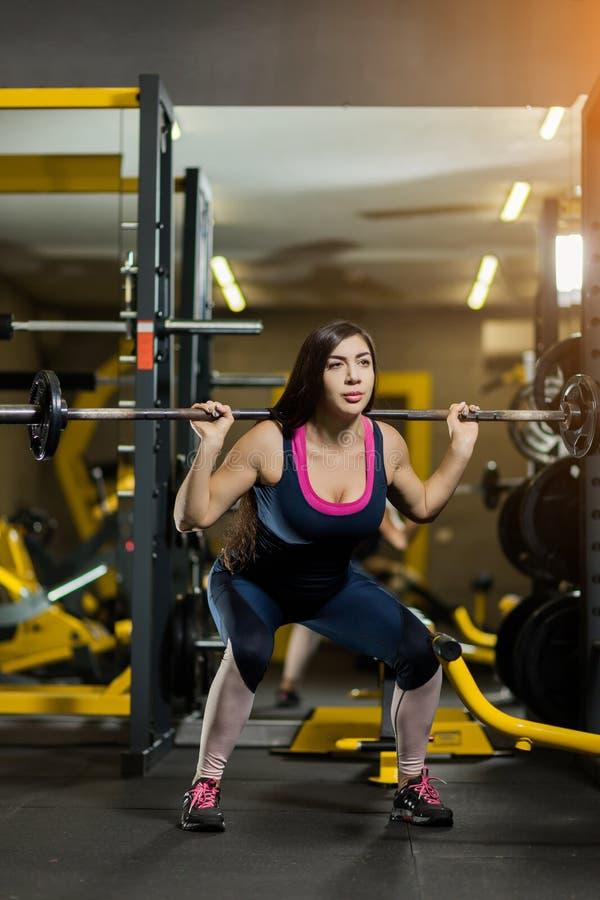 Lyftande vikter för sportig kvinna Färdig flicka som övar byggnadsmuskler Kondition och bodybuilding royaltyfria bilder