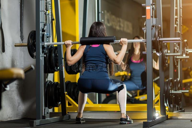 Lyftande vikter för sportig kvinna Färdig flicka som övar byggnadsmuskler Kondition och bodybuilding royaltyfri bild