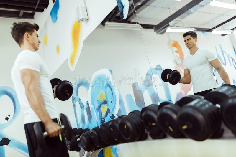 Lyftande vikter för stilig man i idrottshall royaltyfri foto