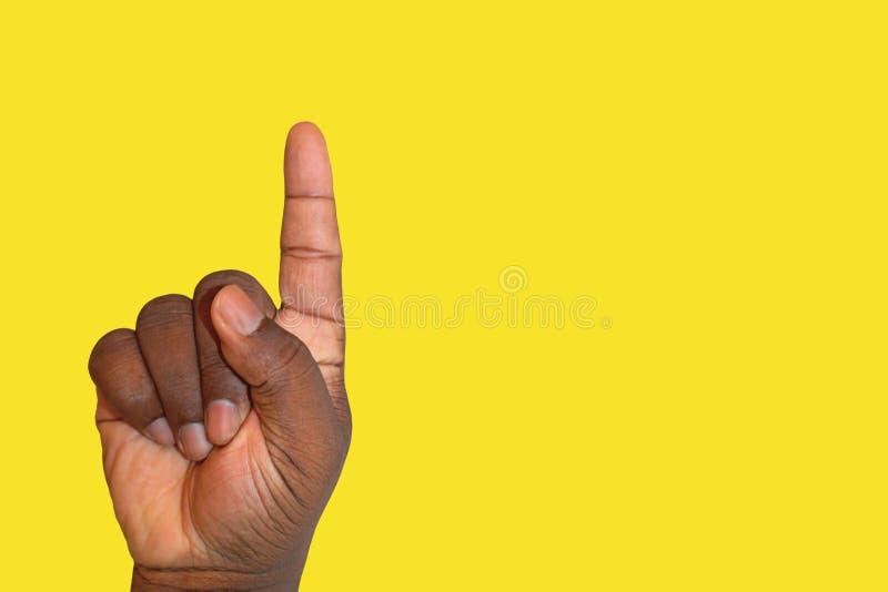 Lyftt hand som frågar för tillåtelse eller svarar en fråga på en gul bakgrund - afrikansk etnicitet royaltyfria bilder
