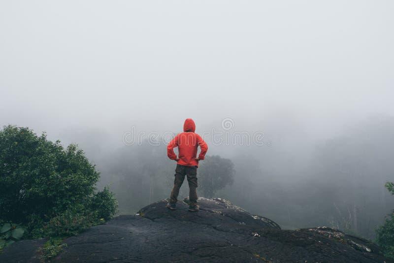 Lyftta händer för handelsresanden som äventyrar mannen står på klippaberg, semestrar för sommar för lopplivsstilbegrepp arkivfoton