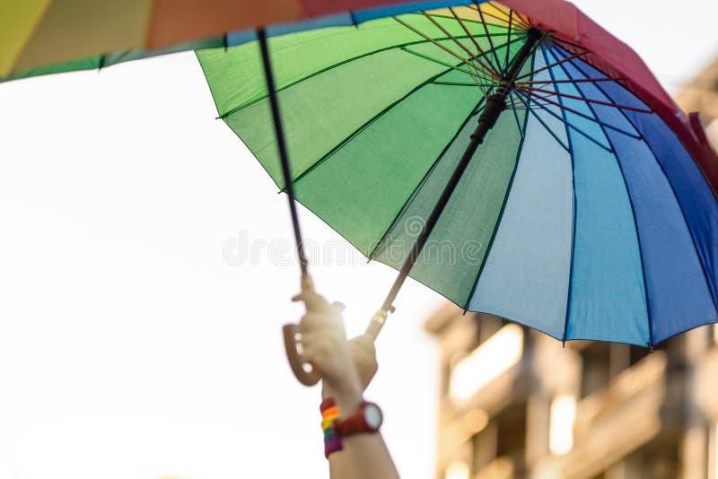 Lyftta händer med regnbågen färgade paraplyer royaltyfri bild