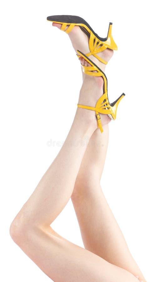 Lyftta sexiga kvinnan för slutet lägger benen på ryggen den upp med gula skor royaltyfria bilder