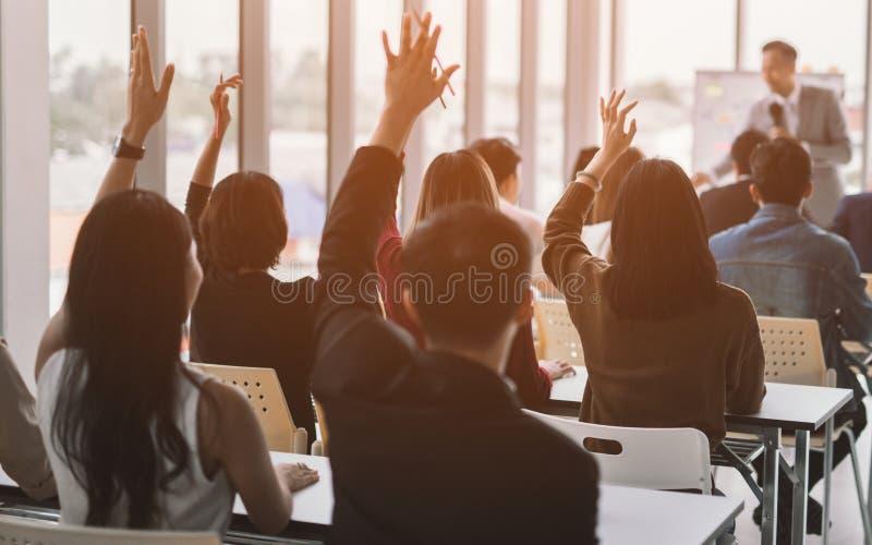 Lyftta upp h?nder och armar av den stora gruppen i seminariumgrupprum att inst?mma med h?gtalaren p? konferensseminariumm?tesrum royaltyfri foto