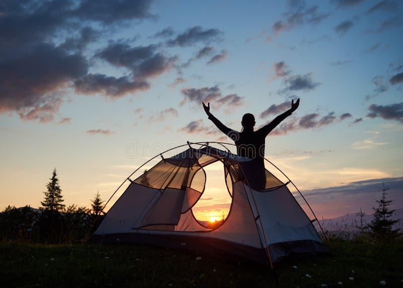 Lyftte det turist- kvinnliga anseendet för kontur med hennes händer himmel överst av berget nära campingplats på solnedgången iso royaltyfri foto