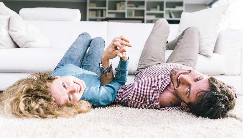 Lyind giovane felice delle coppie sul tappeto immagini stock libere da diritti