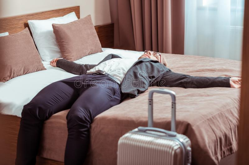 Adult man being in a business trip and staying in a hotel room royalty free stock photo