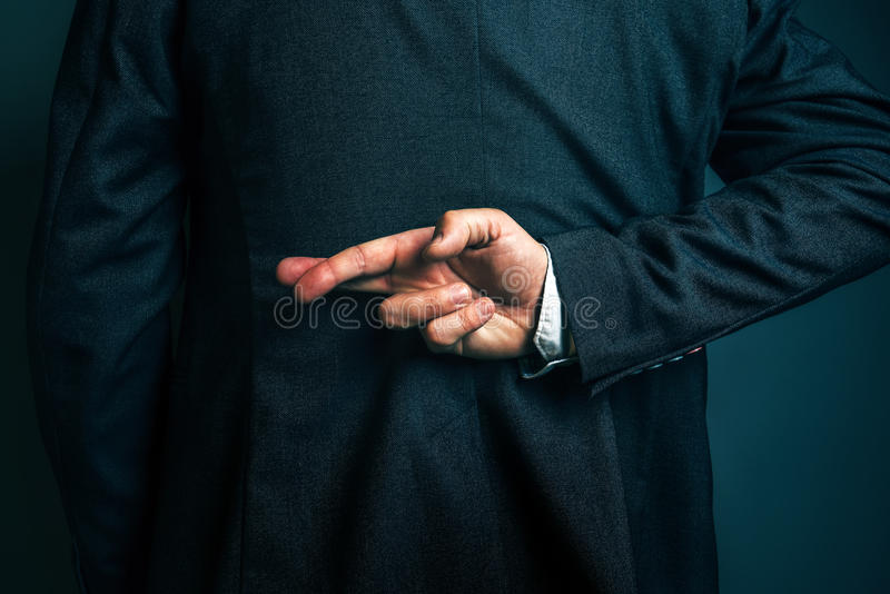 Lying businessman holding fingers crossed behind his back stock images