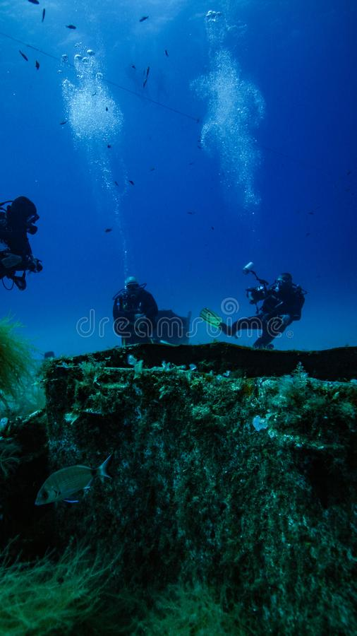 Mid ships on the P31. Three divers in the distance. Lying in the central Mediterranean of the coast of Malta is the wreck of a sunken patrol boat the P31. This royalty free stock photography