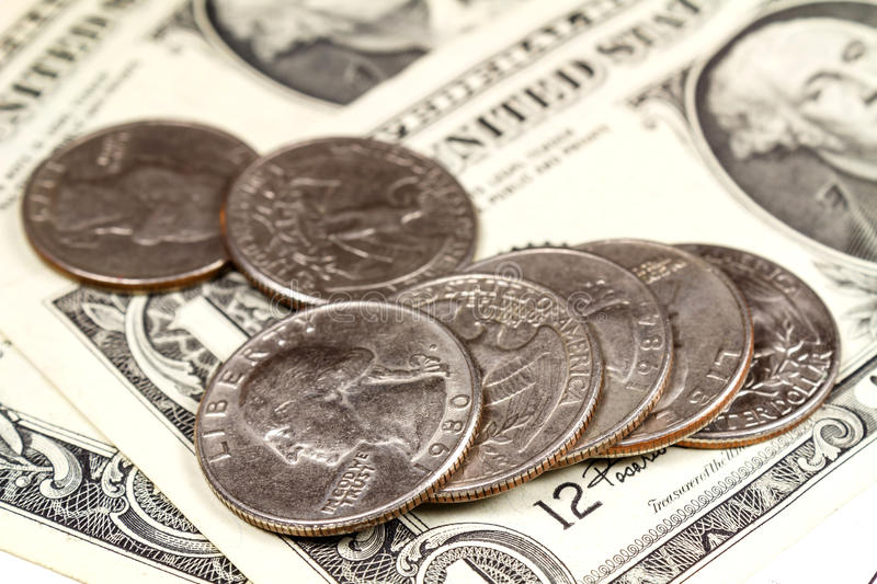 Lying coins on the US dollars banknotes. Focus in the foreground royalty free stock photo