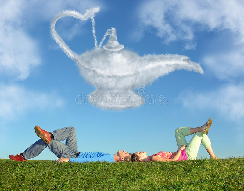 Lying couple on grass and dream alladin lamp cloud stock photo