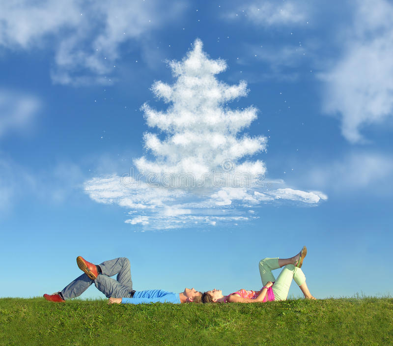 Lying couple on grass and dream christmas tree stock photography