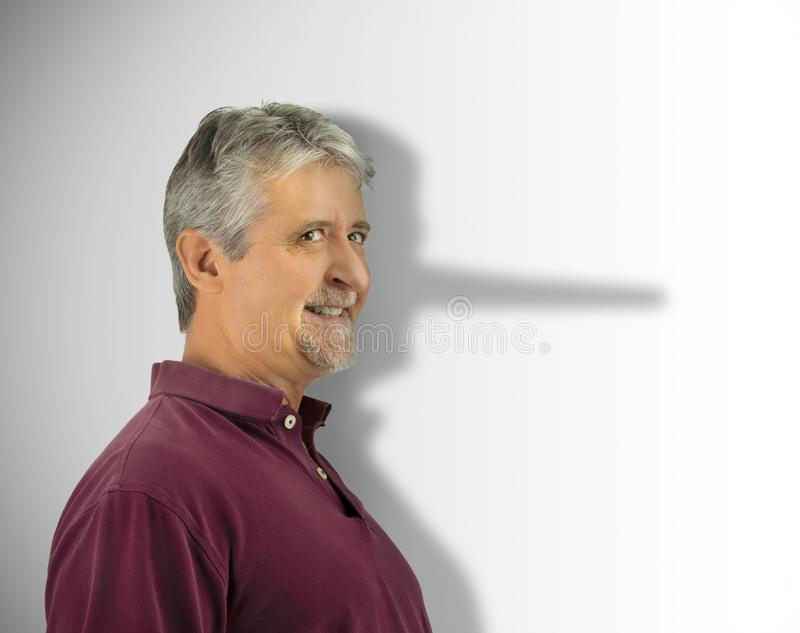 Lying dishonest man with his growing long liar Pinocchio nose showing in his shadow royalty free stock photography