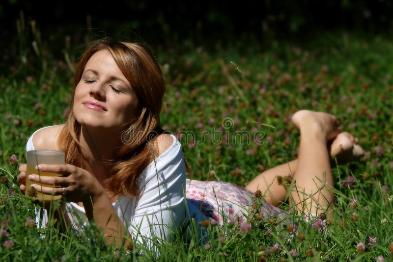 Lying girl. Relaxing girl in the grass with cup of tea royalty free stock photos