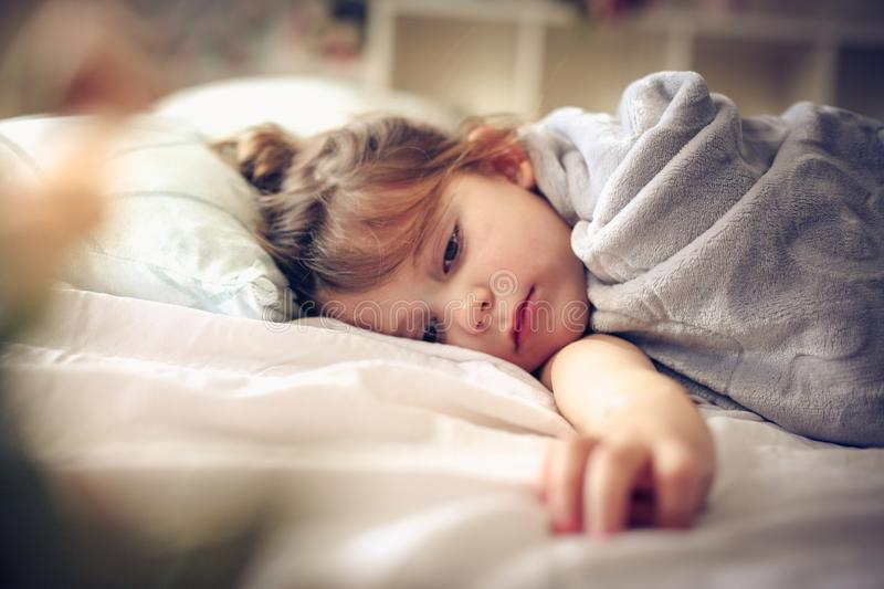 Lying i bed. Little girl lying in bed. Space for copy stock photos