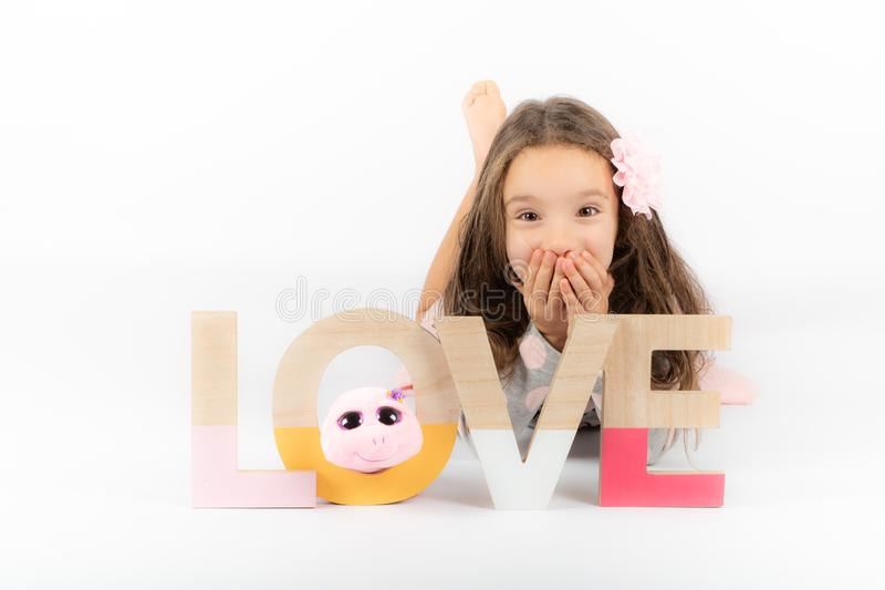 Little girl lying down and inscription love stock images