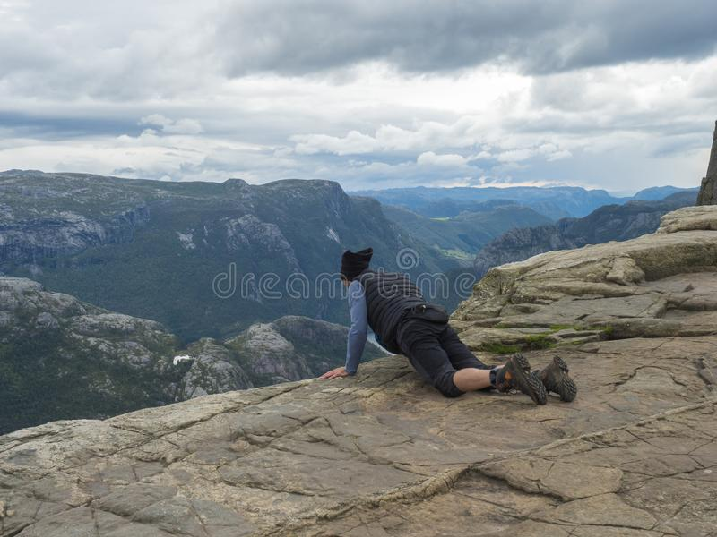 Lying men looking view on fjord Lysefjord over the Preikestolen cliff, famous Norway viewpoint. Moody autumn day. Nature royalty free stock image