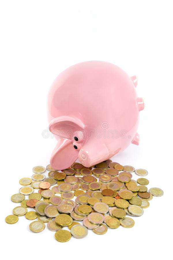 Lying pink piggy bank with pile of euro coins royalty free stock photos