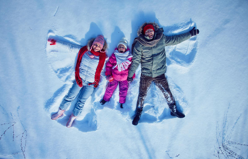 Lying in snowdrift. Young couple and cute little girl having fun in snowdrift royalty free stock photo