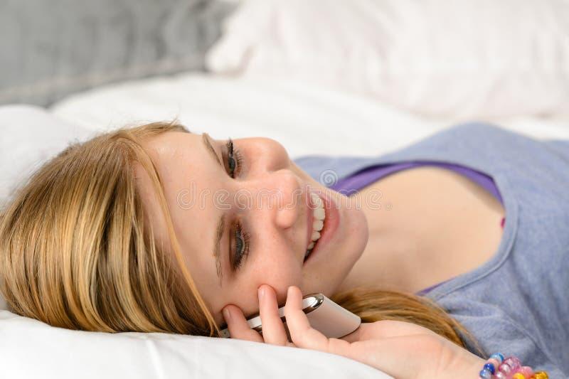 Lying teenager girl talking on her phone