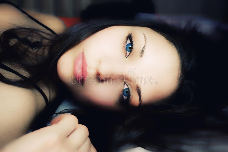 Lying woman with dark blue eyes. Beautiful lying woman with dark blue eyes royalty free stock photography