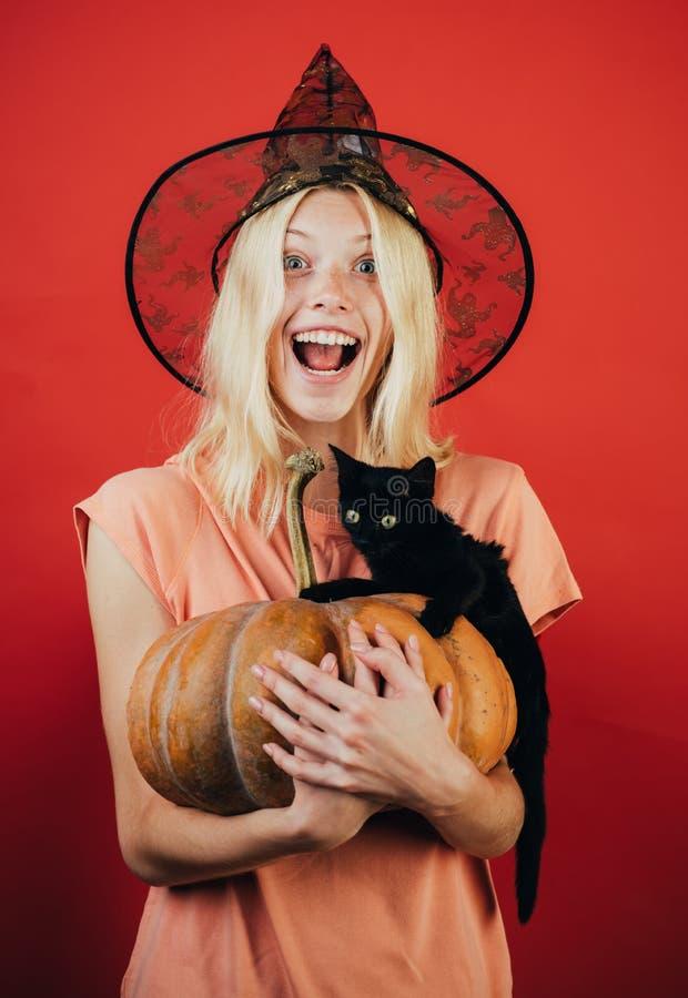 Lykta för pumpahuvudstålar Sniden pumpa - roligt begrepp Uttrycksframsida - förvånad kvinna Den svarta katten sitter på en pumpa arkivbild
