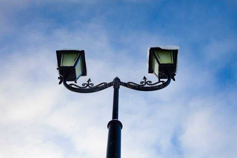Lykta i vinter mot den blåa himlen med moln royaltyfria bilder