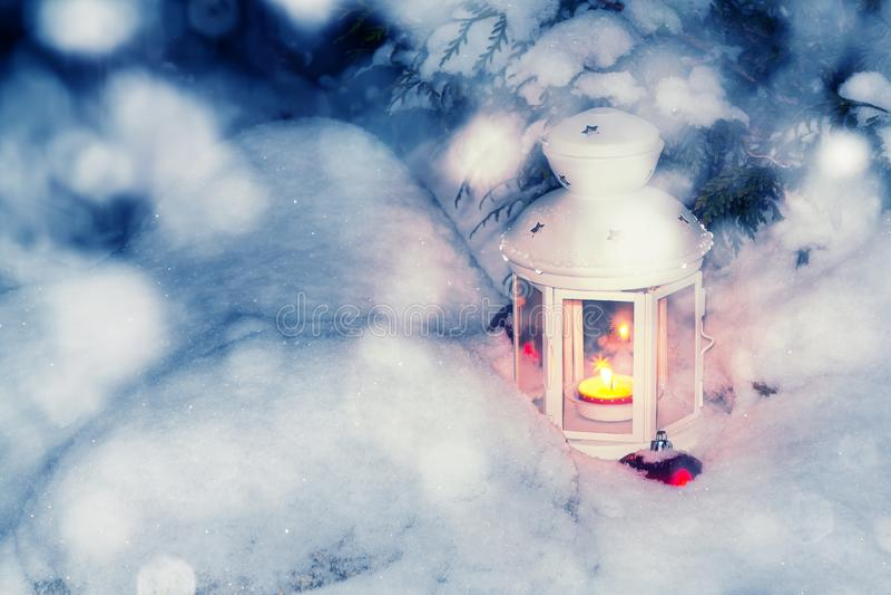Lykta med en brinnande stearinljus under entäckt julgran i borggården av huset i snödrivorna royaltyfri fotografi