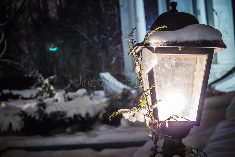 Lykta med snö och en filial av ett glödande gult ljus för julgran Snö på lyktan, vinterafton i parkerar royaltyfria foton