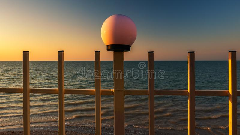 Lykta mot bakgrunden av soluppgången på havet fotografering för bildbyråer