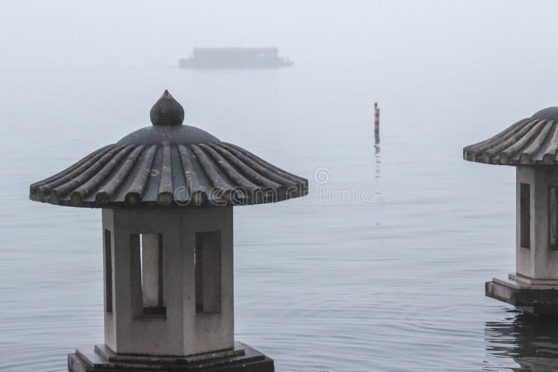 Lykta på sjön i dimman arkivfoto