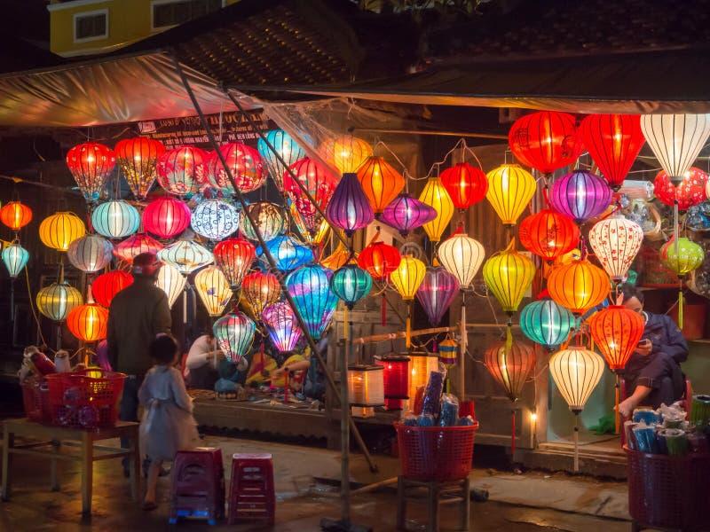 Lyktasäljare i gatorna av den forntida staden av Hoi An i centrala Vietnam, färgrika lyktor som hänger överallt att skapa ett sto royaltyfri bild