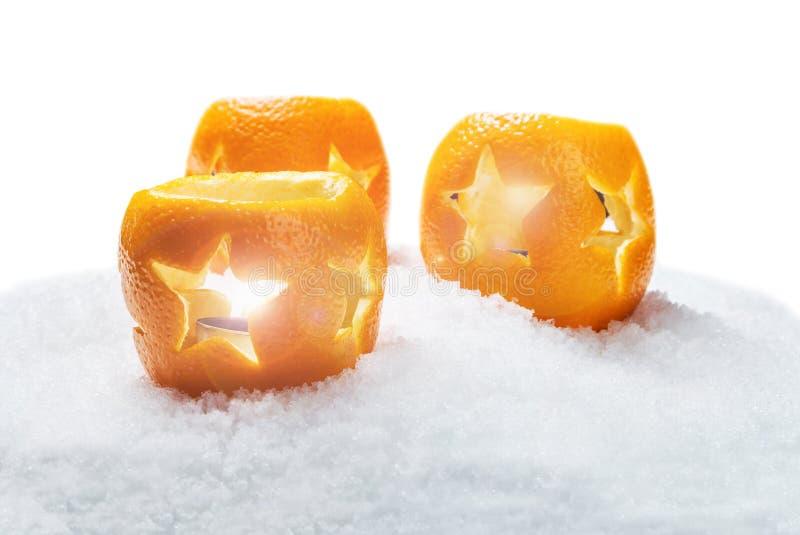 Lyktor av apelsinjulpynt i snön arkivbild