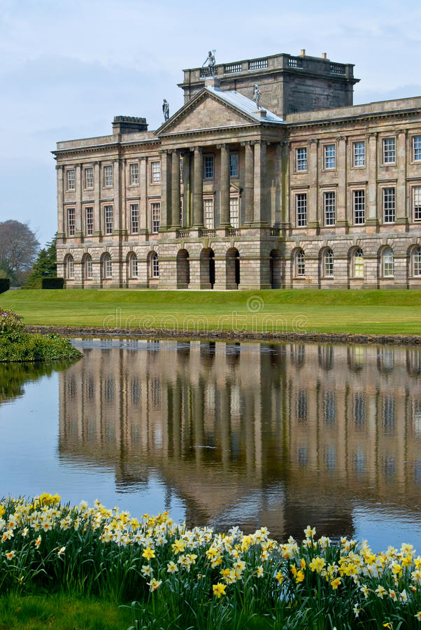 Lyme Hall in Spring. Lyme Hall building in Lyme Park, Cheshire, shot across a late with daffodils in the foregroundn royalty free stock photos