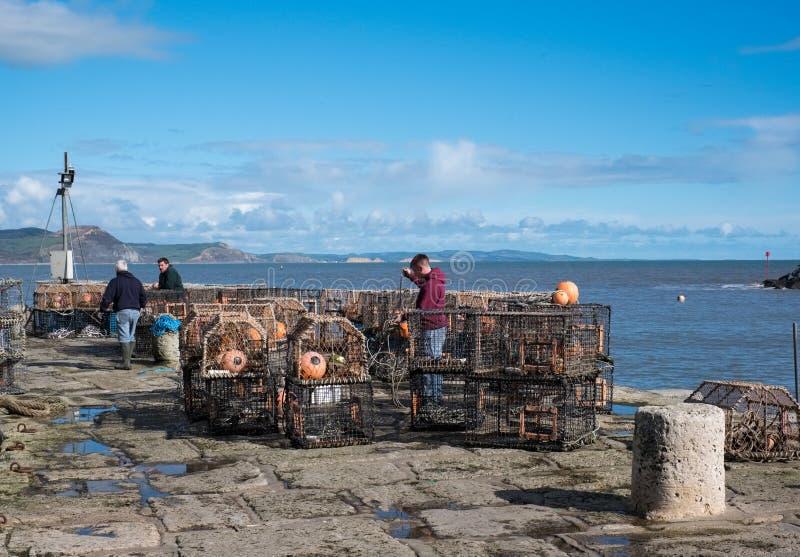 LYME REGIS, DORSET/UK - MARS 22: Fiskare som reparerar deras Lob arkivfoto