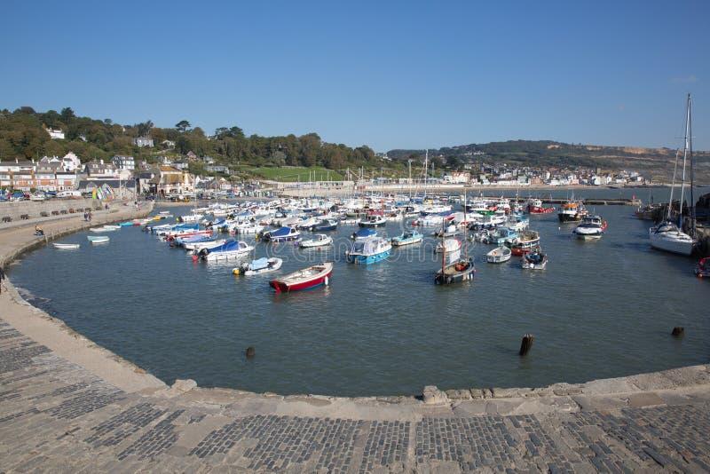 Lyme Regis hamn Dorset England UK med fartyg på en härlig för stillhet dag fortfarande på den engelska Jurassic kusten arkivbilder