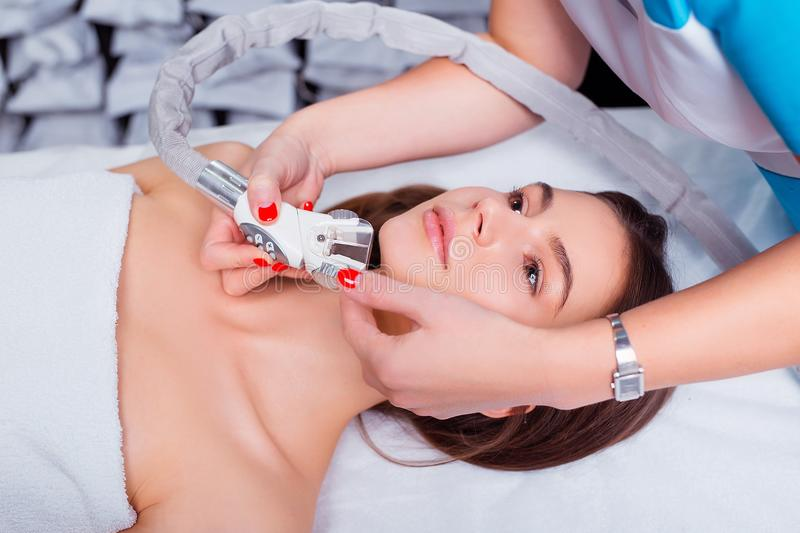 Lymphatic drainage massage LPG apparatus process. Therapist beautician makes a rejuvenating facial massage for the woman royalty free stock image